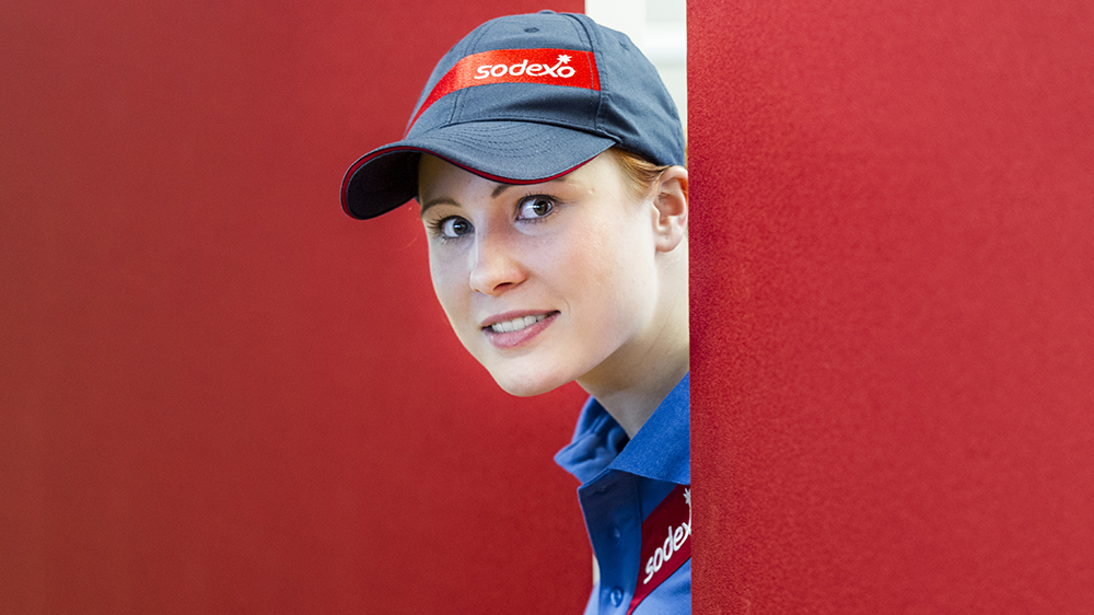 Sodexo employee looking around a red wall
