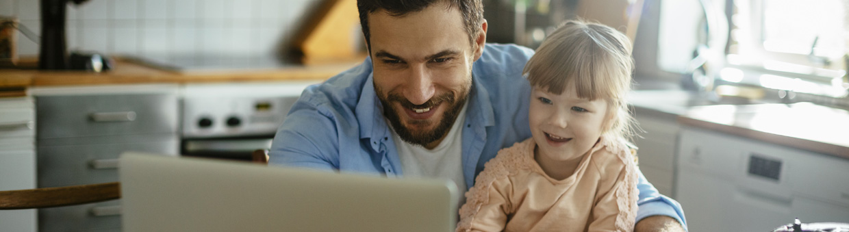 Father and daughter looking at laptop
