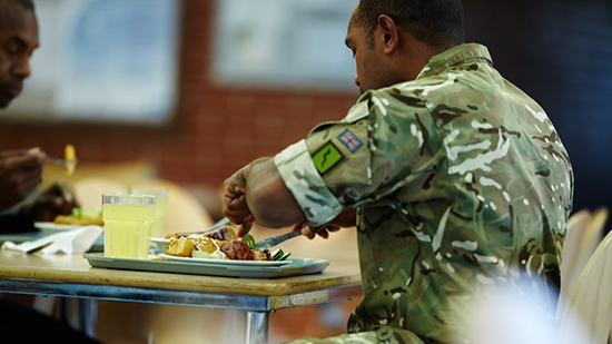 man sat eating food at defence site