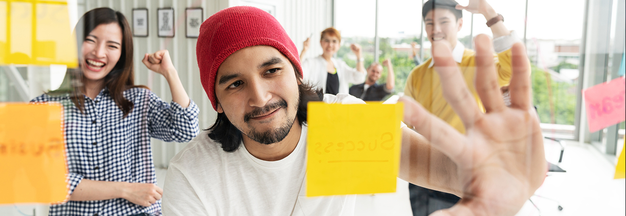 Man pointing at post-its on a clear board