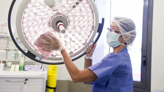 Woman biocleaning in a hospital operating theatre
