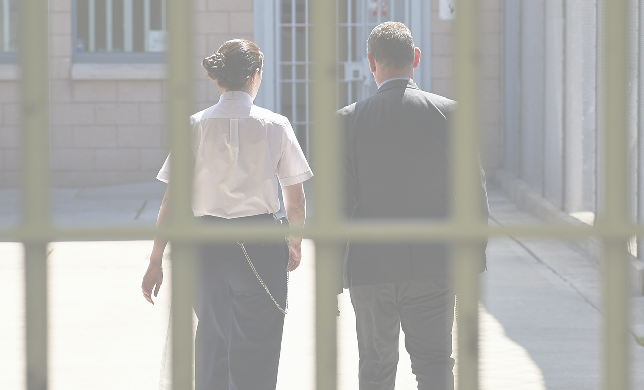 A male and a female prison officer walking through a prison, prison bars in the foreground