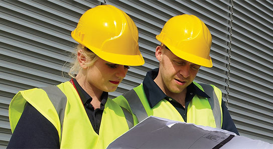 Woman and man in hard hats looking at construction plans
